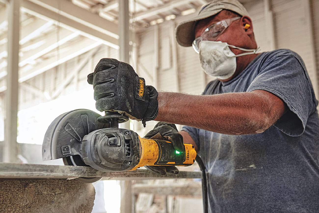 man cutting with a hand held grinder