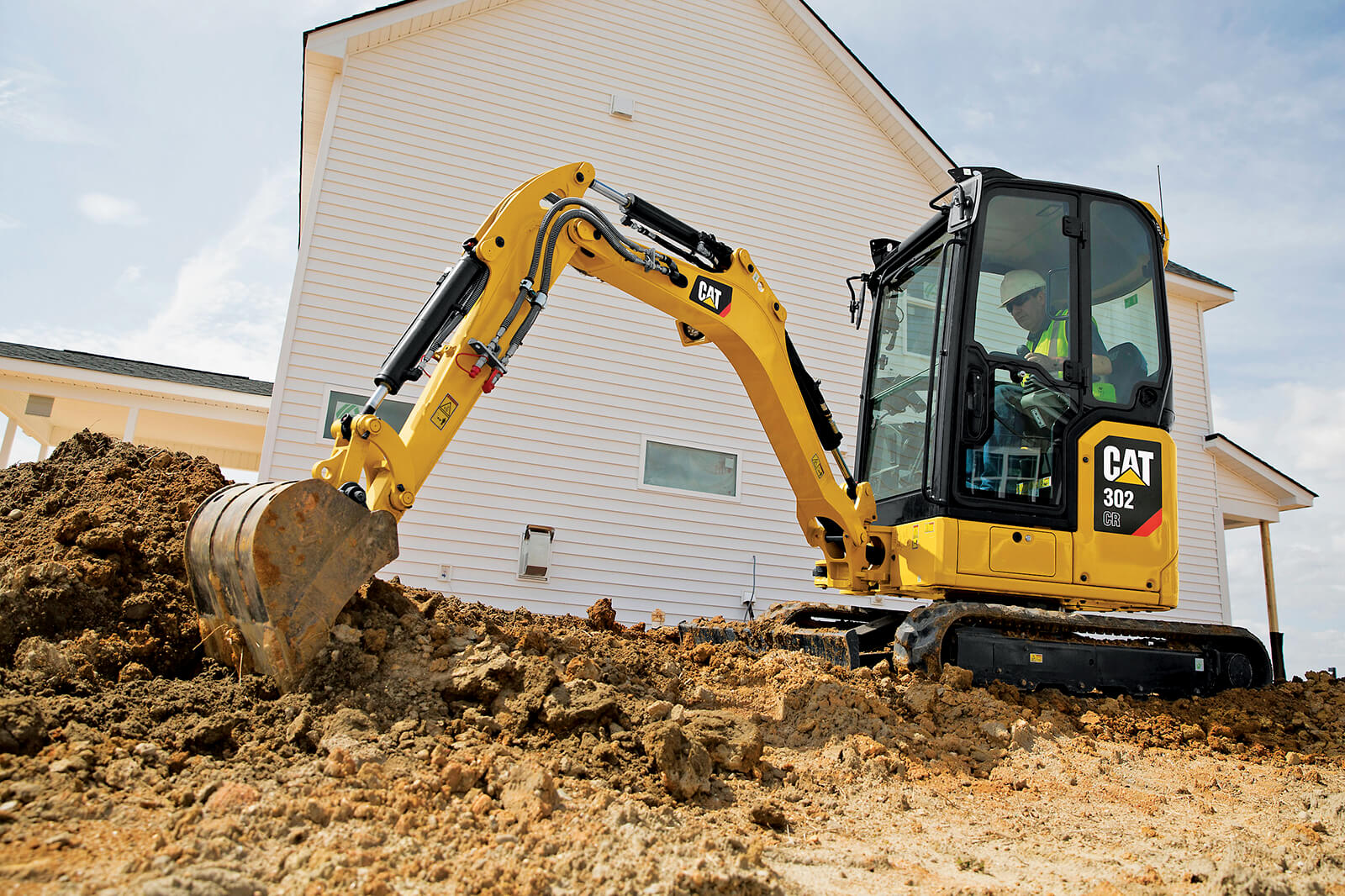 mini excavator working beside a house