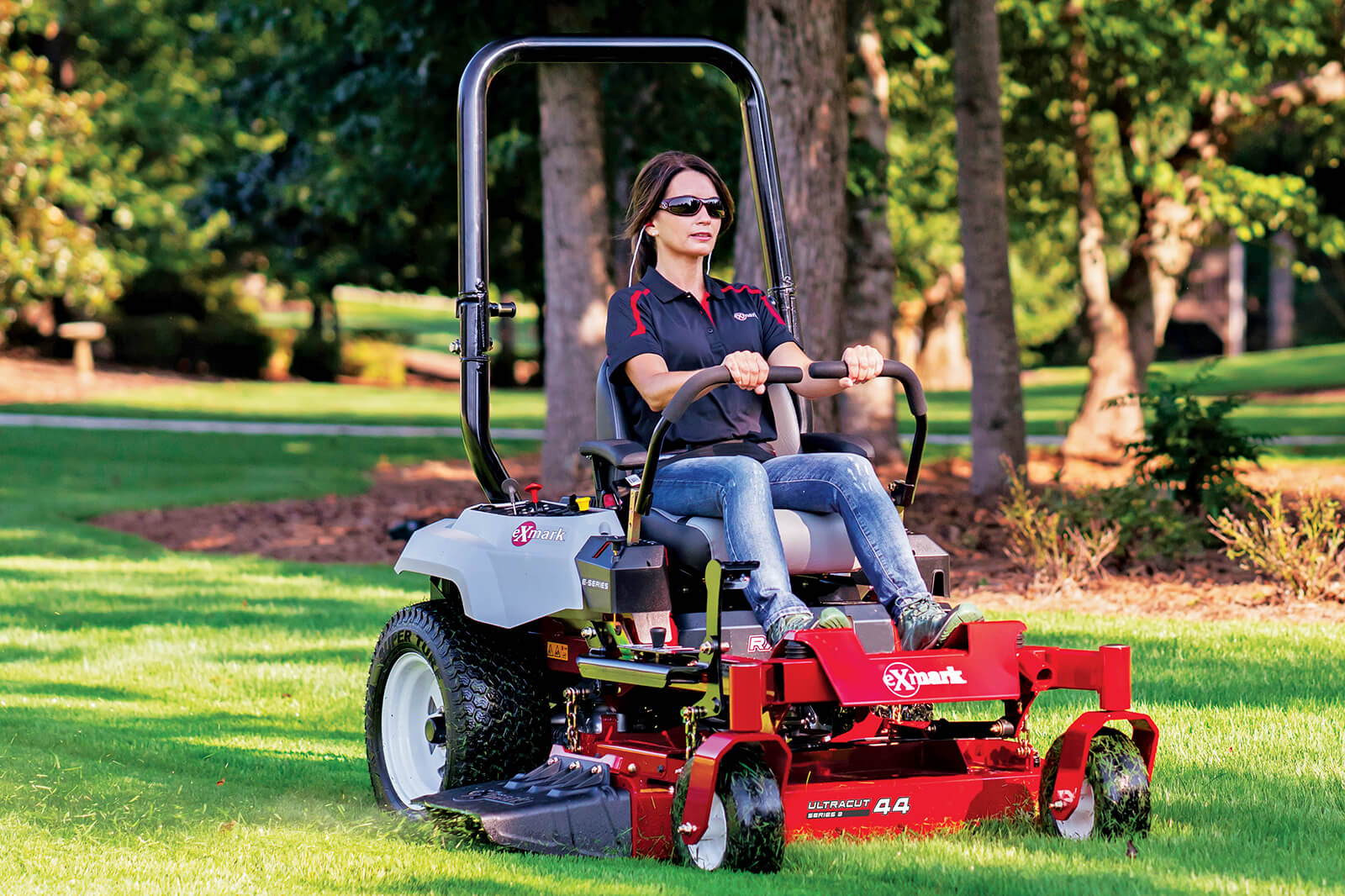 woman using a riding mower to cut grass