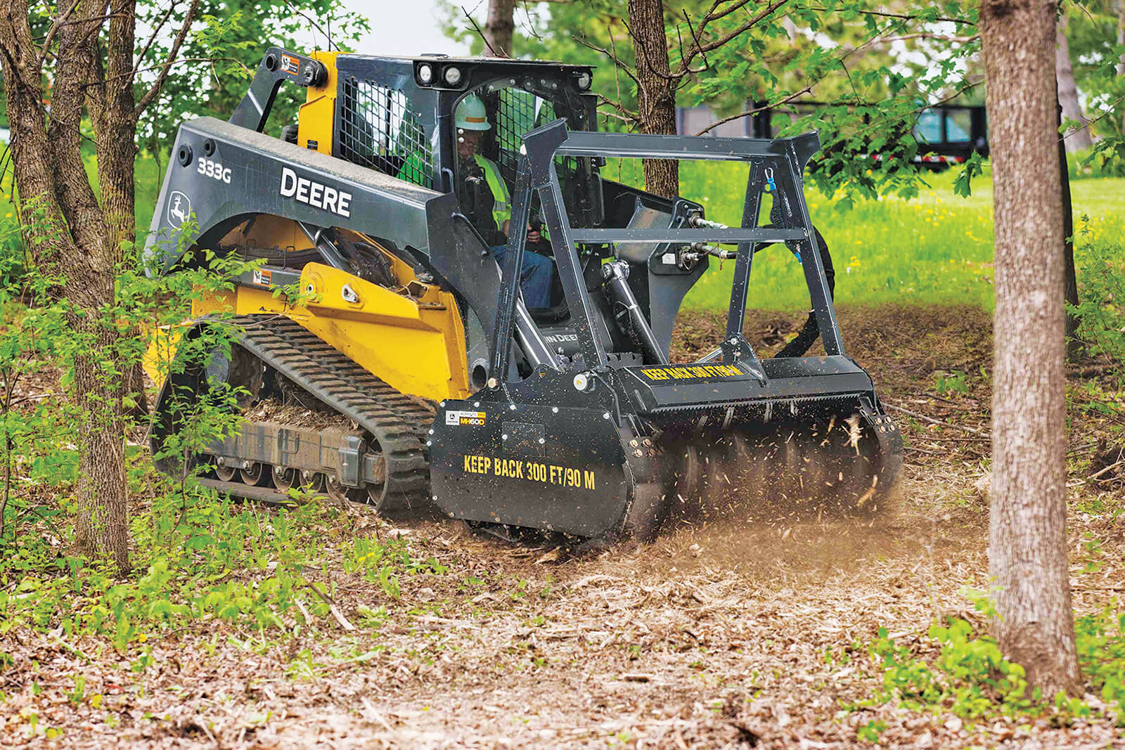 skid steer in the forest sing an attachment