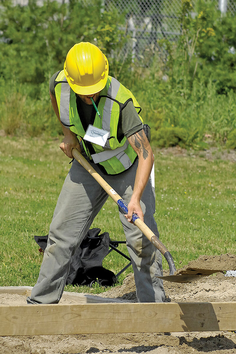 man in construction clothes performing a test of ability outside